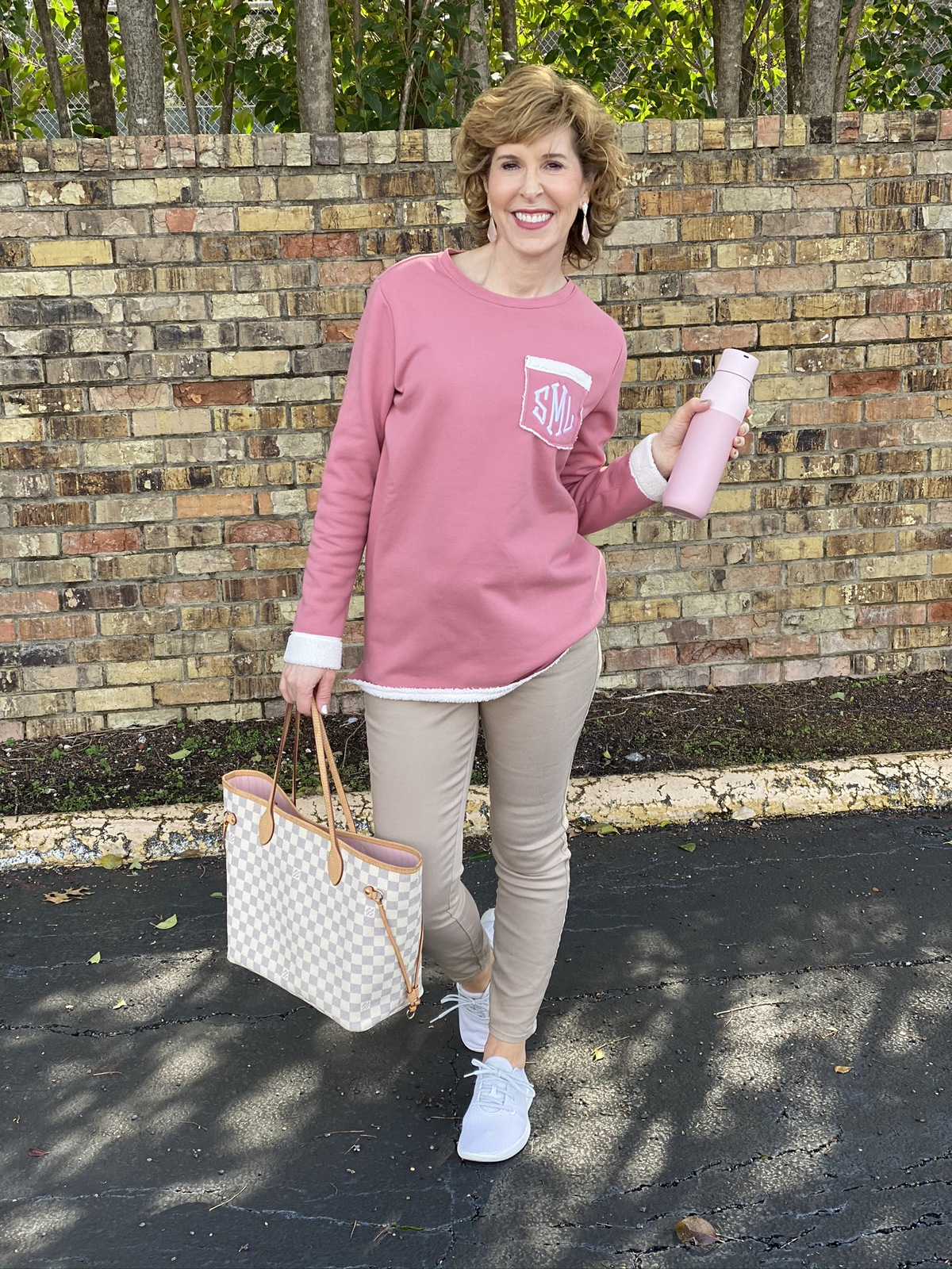 woman in pink monogrammed sweatshirt holding a pink reusable water bottle to help with hydration and immuity standing in front of a brick wall