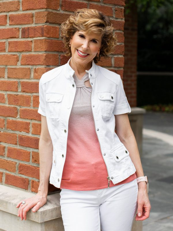 woman leaning against brick pillar wearing ombre top and white short sleeve jacket