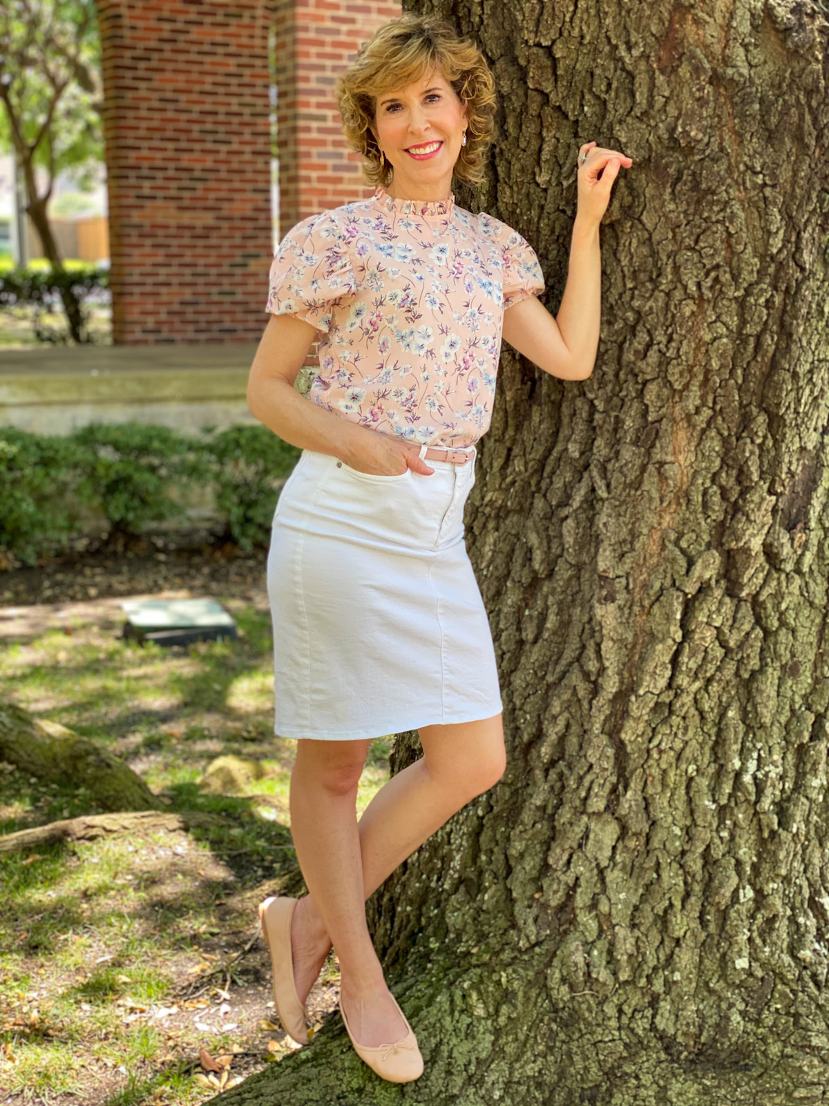 empty nester in pink floral top and white skirt standing by a tree thinking about her purpose as an empty nester