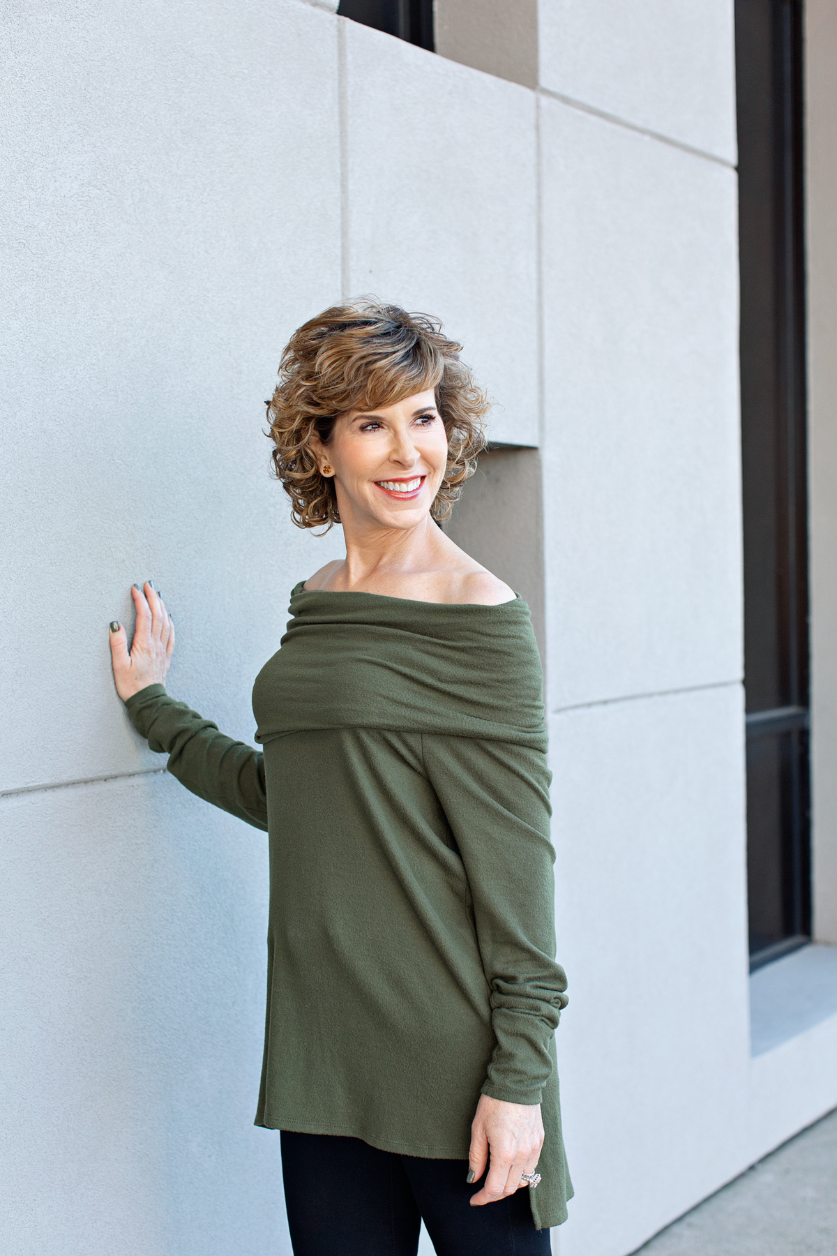 stylish woman over 50 with off the shoulder top standing by building