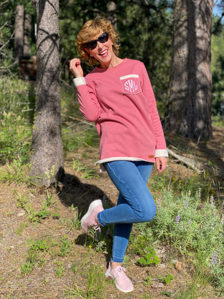 woman wearing marley lilly pink fleece sweater posing in the woods