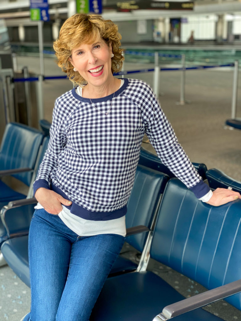woman wearing draper james navy and white gingham sweatshirt posing in the denver airport
