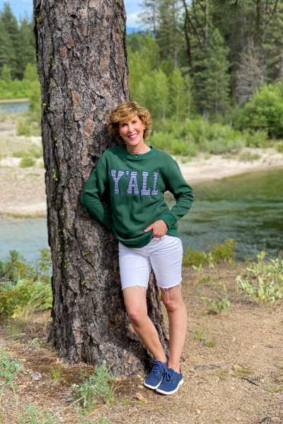 woman wearing marley lilly y'all sweatshirt posing by a pine tree