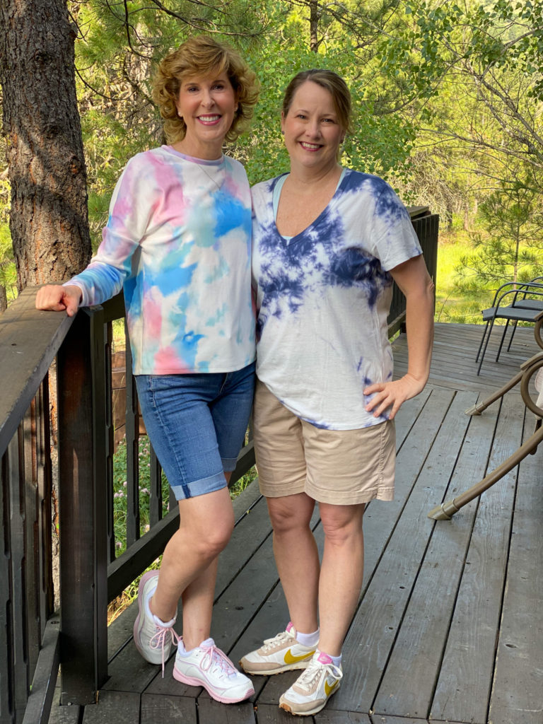 two women dressed in tie-dye shirts standing on the deck of a cabin in the woods