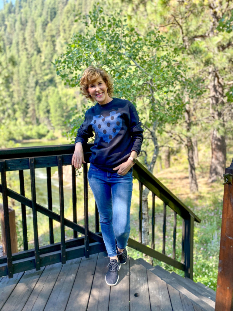 woman wearing black sweatshirt with blue heart standing on deck of a cabin in the woods
