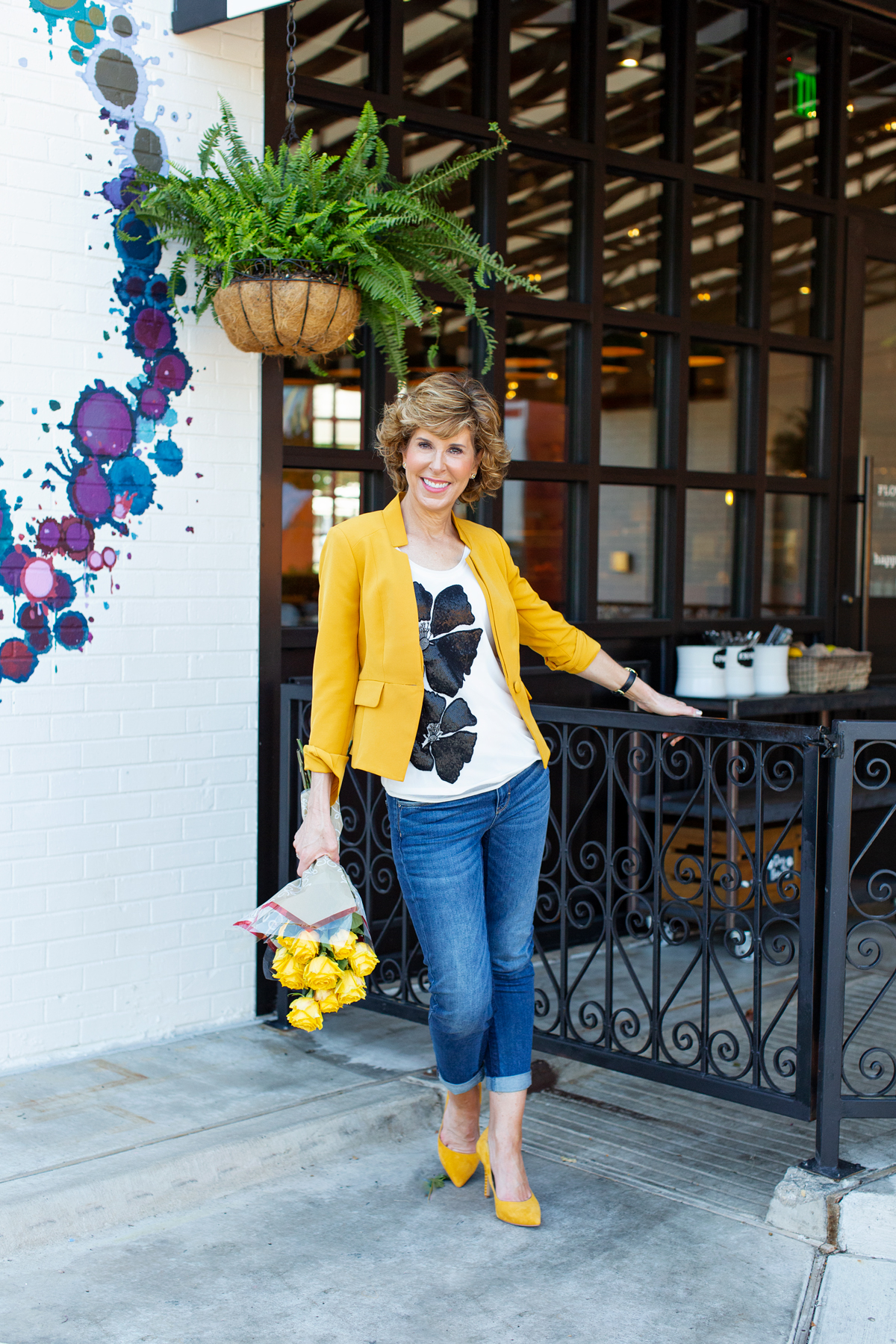 woman with curly hair in yellow blazer holding yellow flowers standing at black gate