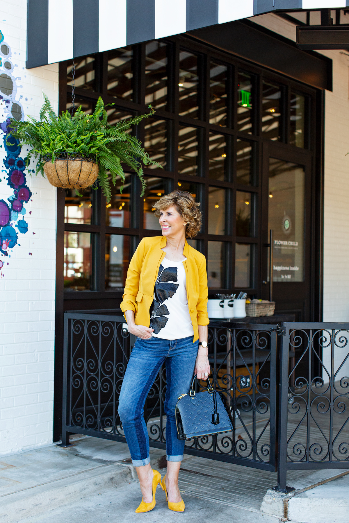 woman with curly hair in yellow blazer holding yellow flowers standing in front of bblack gate