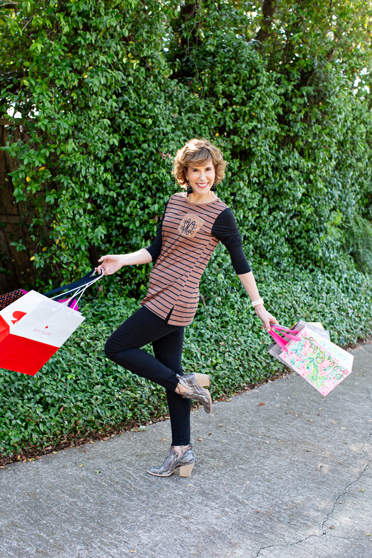 woman carrying multiple shopping bags and spinning around