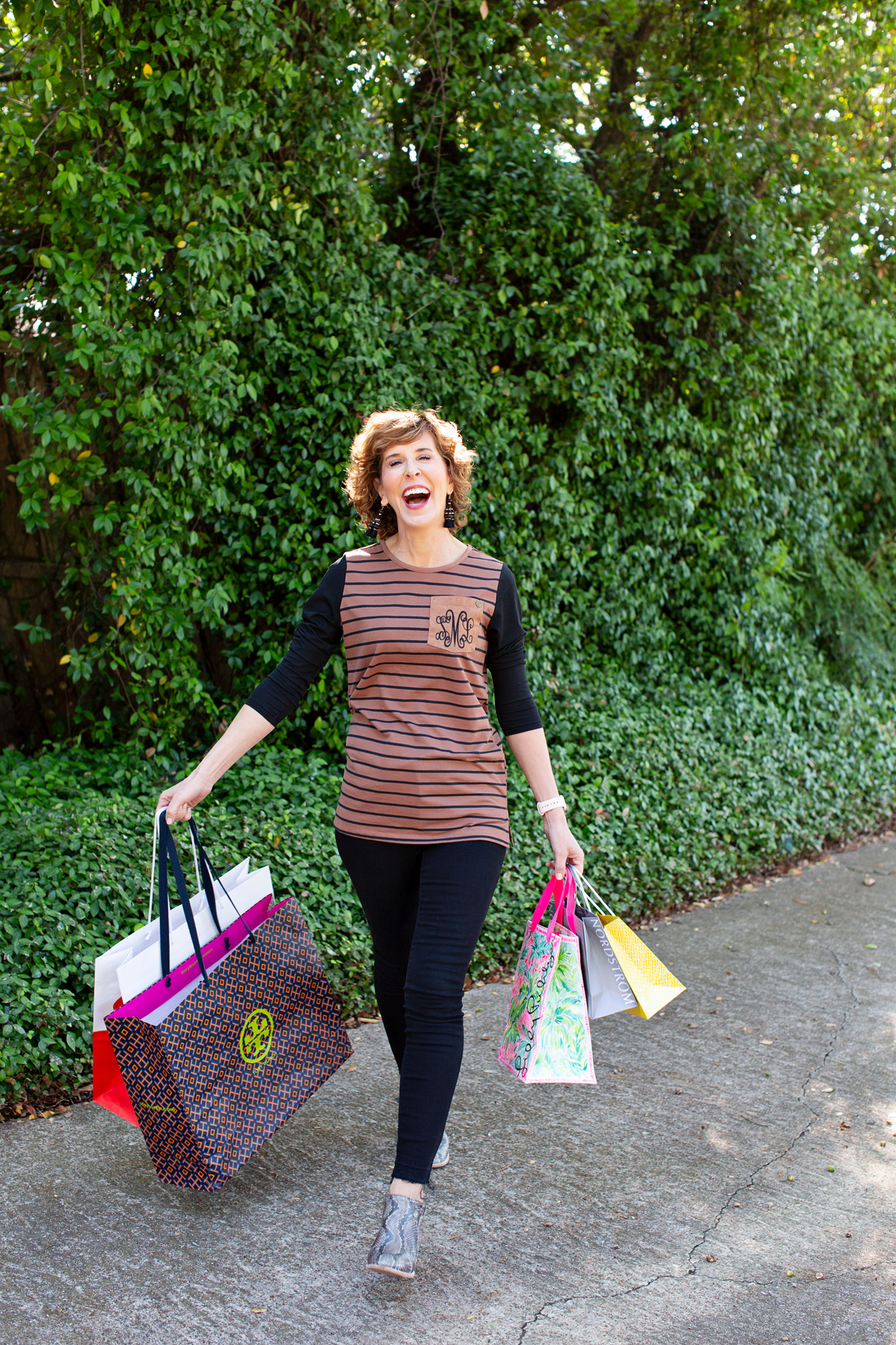 woman walking in the park carrying lots of shopping bags and laughing