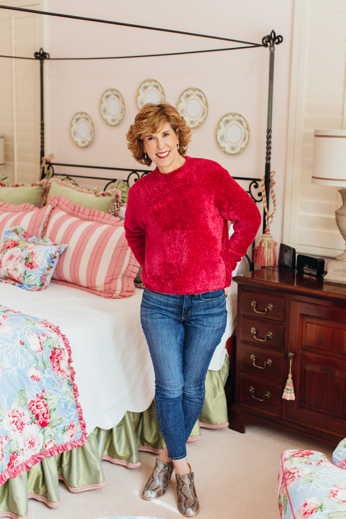 woman in pink fuzzy sweater and jeans posing in her bedroom