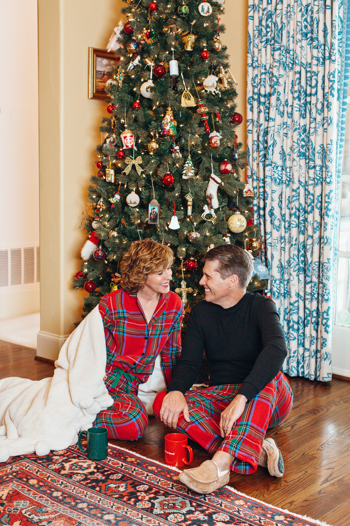 woman and man in red holiday pajamas sitting in front of Christmas tree