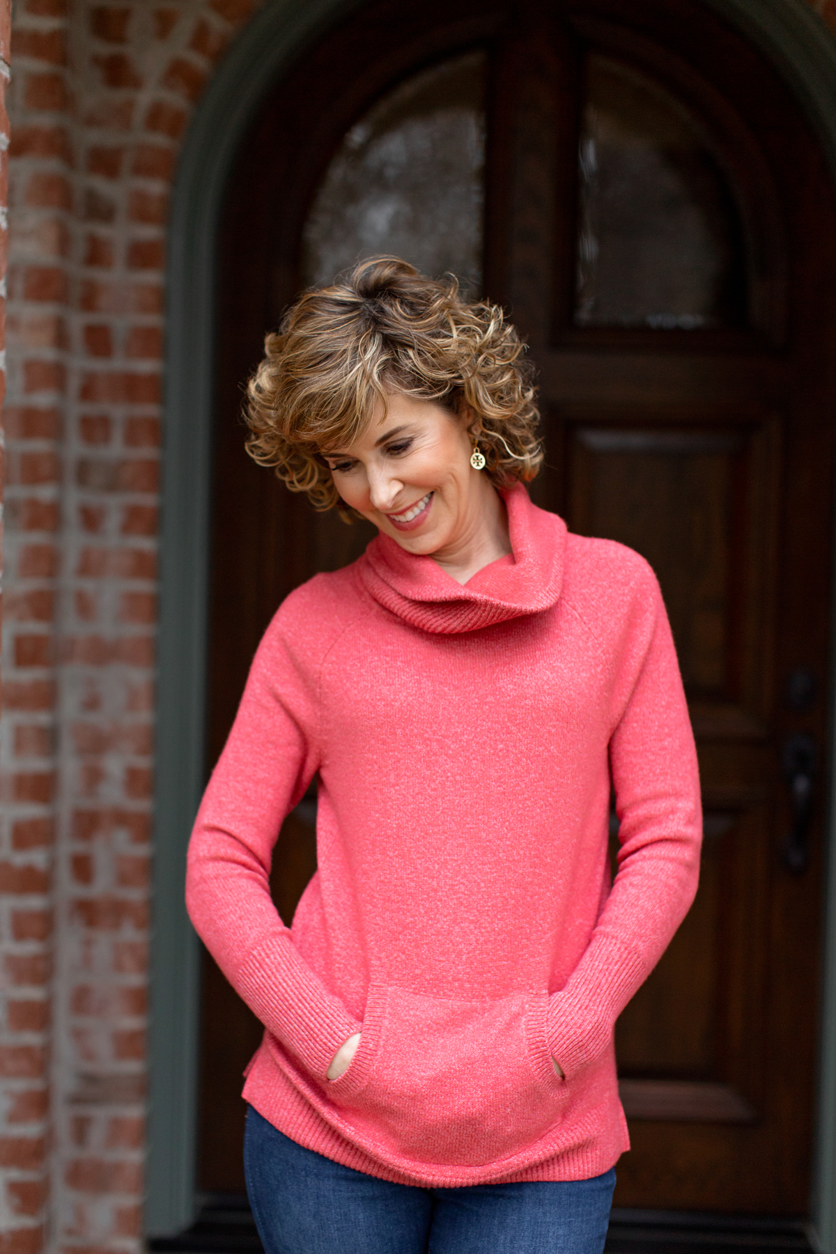 woman in coral turtleneck looking down