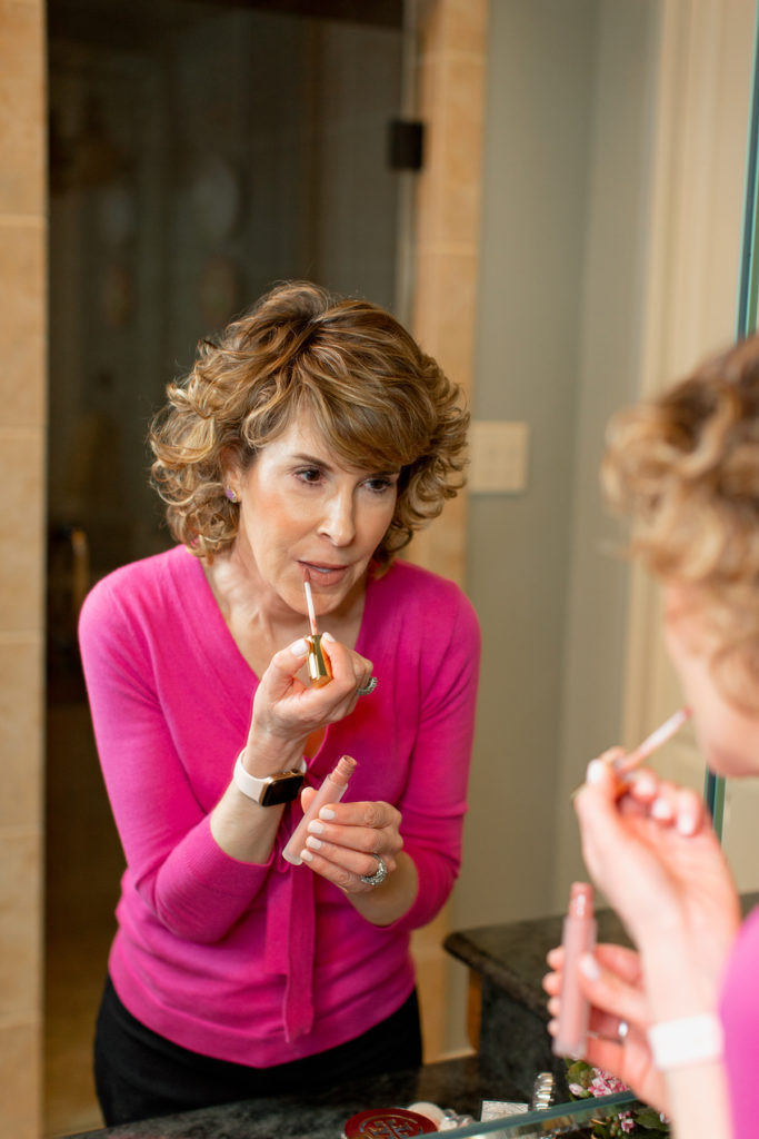 woman over fifty applying lip gloss in mirror