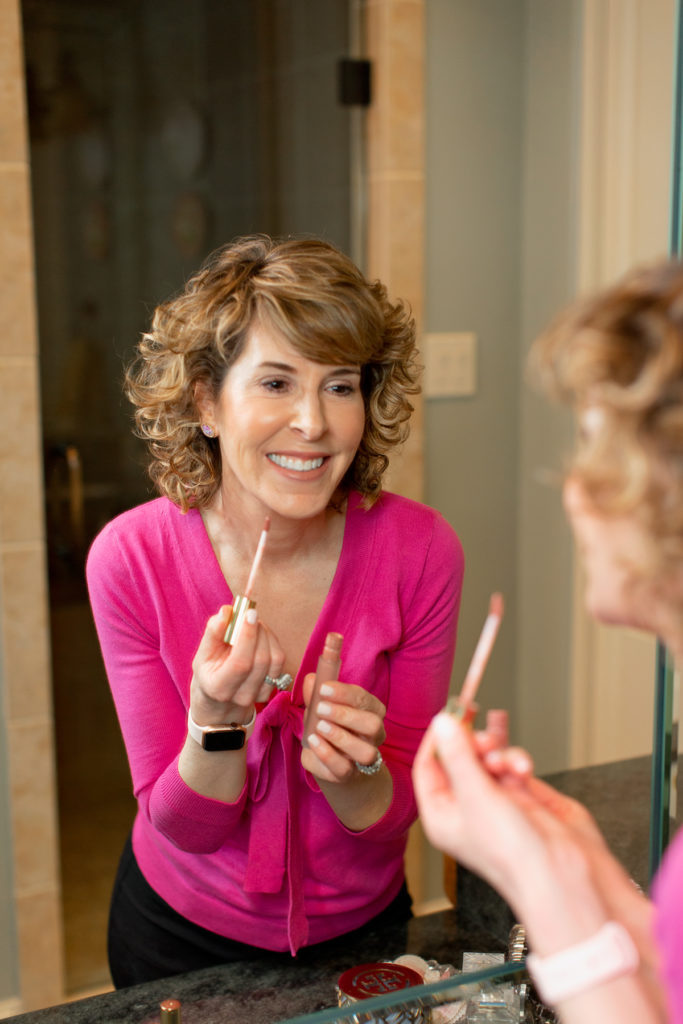 smiling woman over fifty looking in mirror holding lip gloss