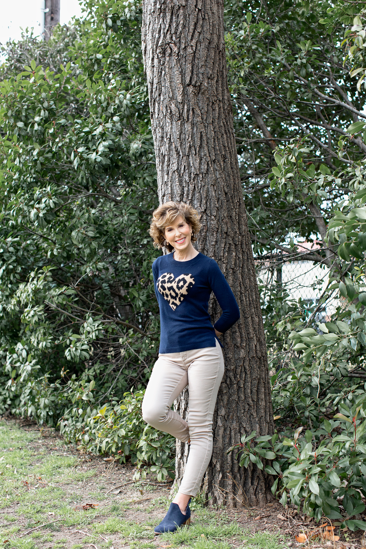 woman in heart sweater leaning against a tree