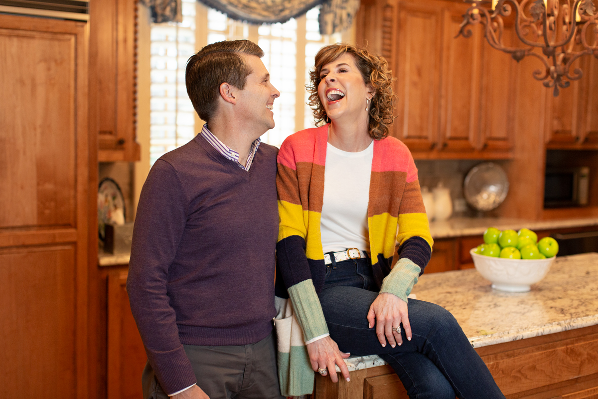 laughing woman sitting on counter in kitchen man standing next to her