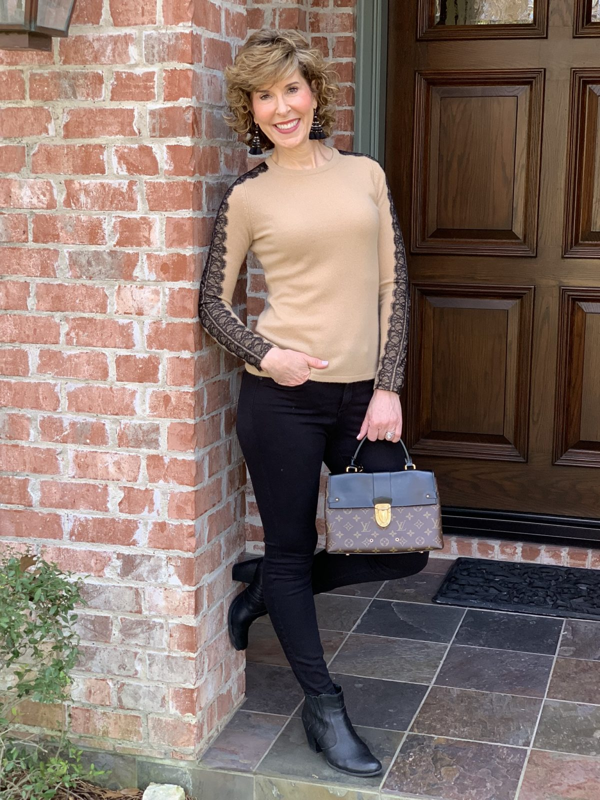 woman standing in archway wearing tan sweater and black pants