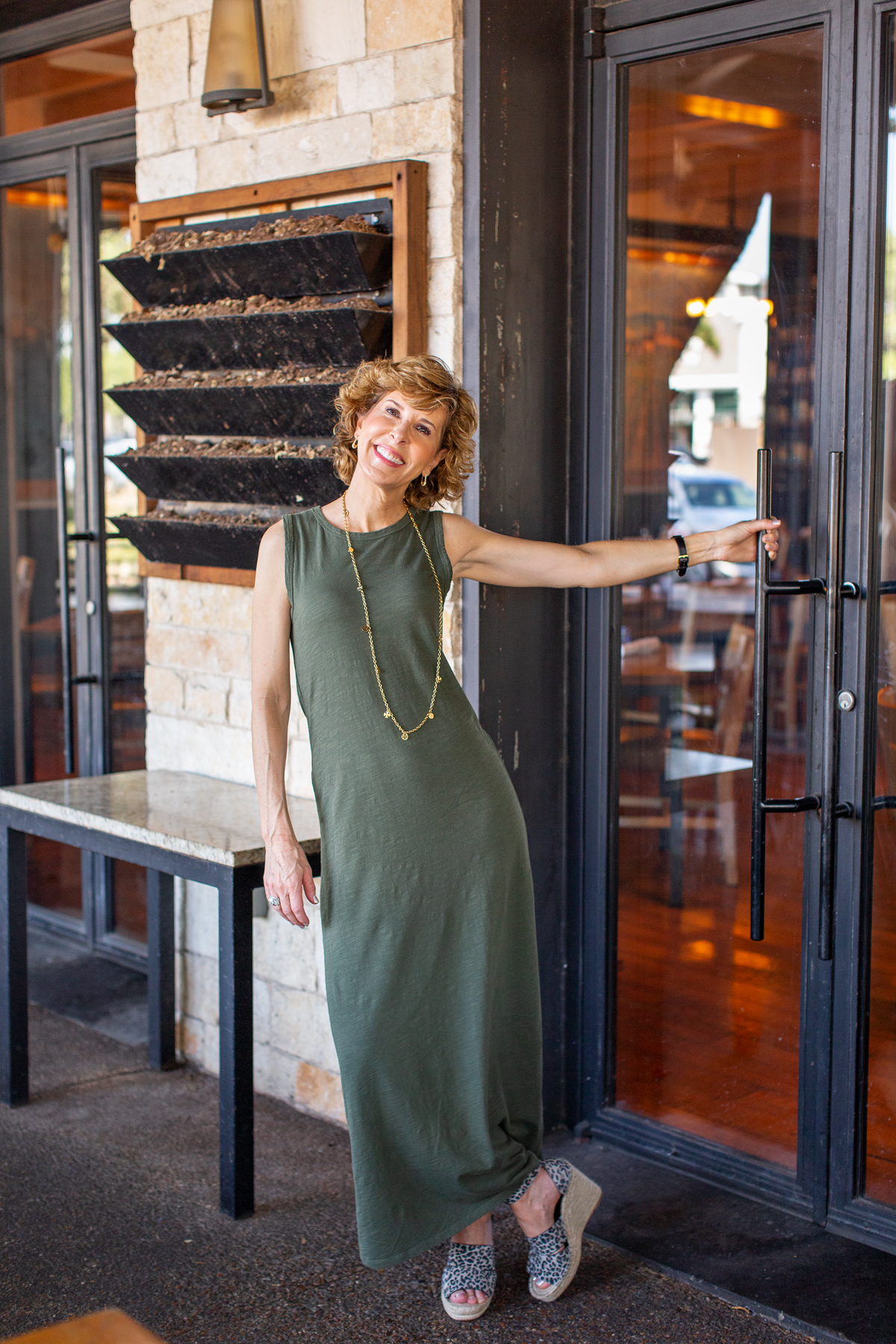 woman in green maxi dress standing at a door on a restaurant patio
