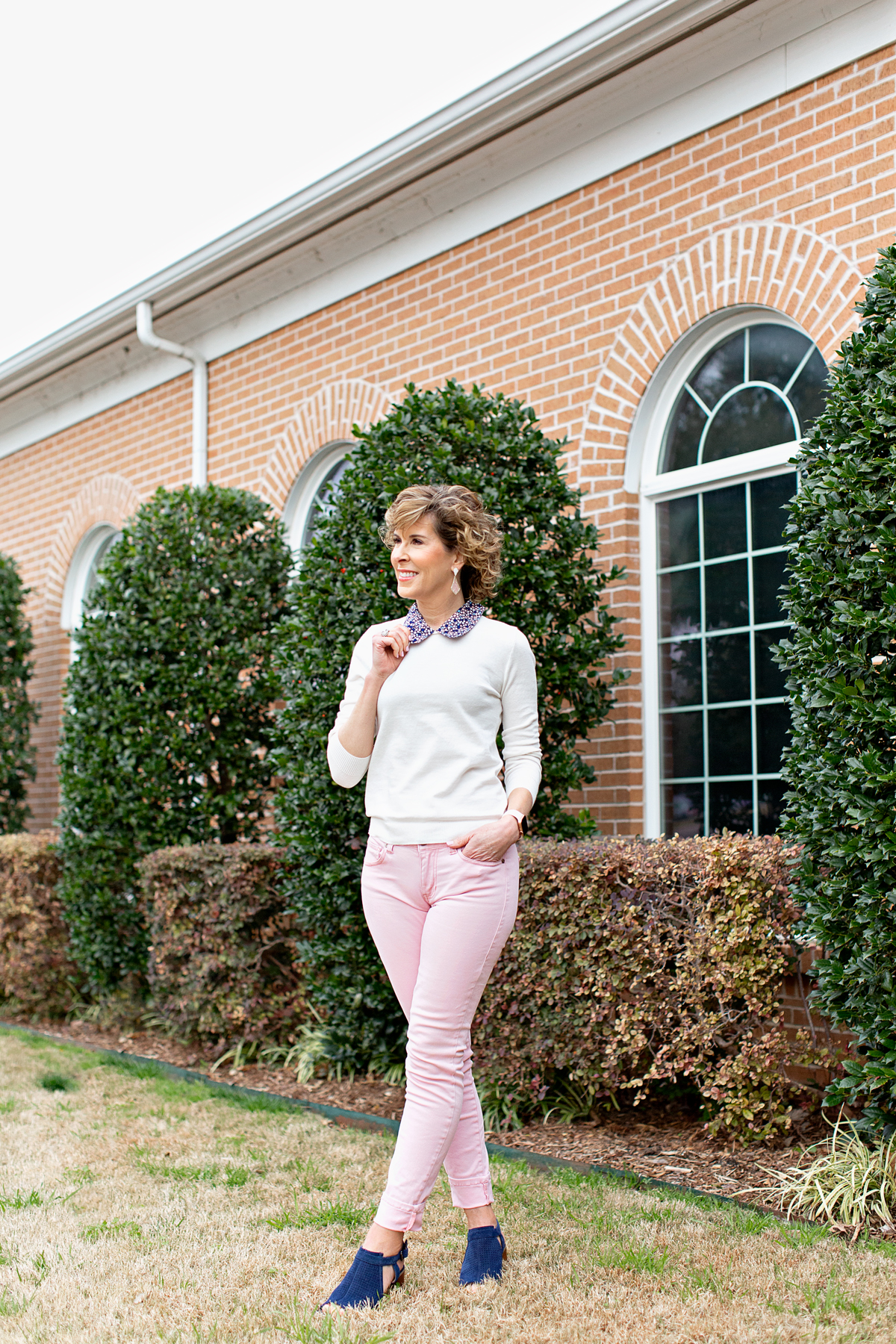 woman wearing pink jeans and holding the blue collar of white sweater