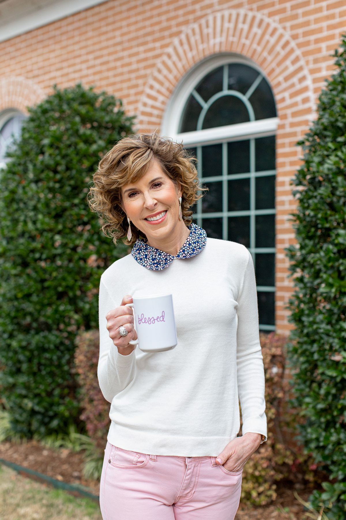 woman wearing white sweater with blue collar holding a coffee cup