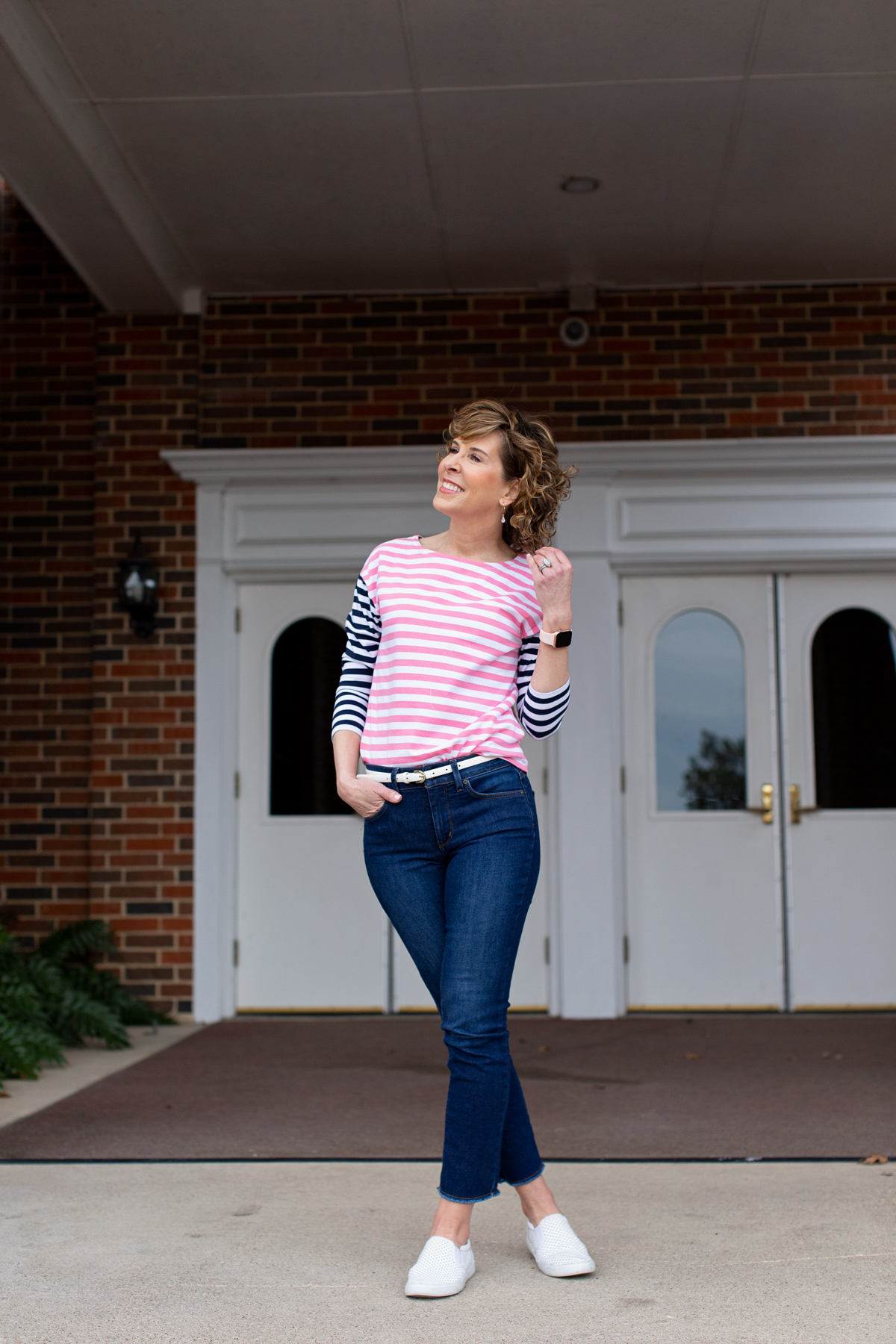 woman wearing striped shirt standing in front of white doors