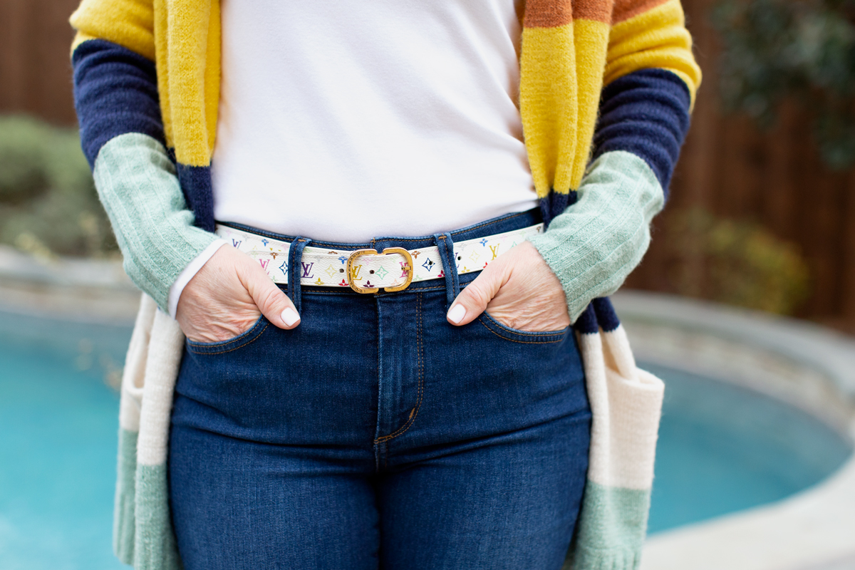 womans wearing designer belt with hands in jean pockets