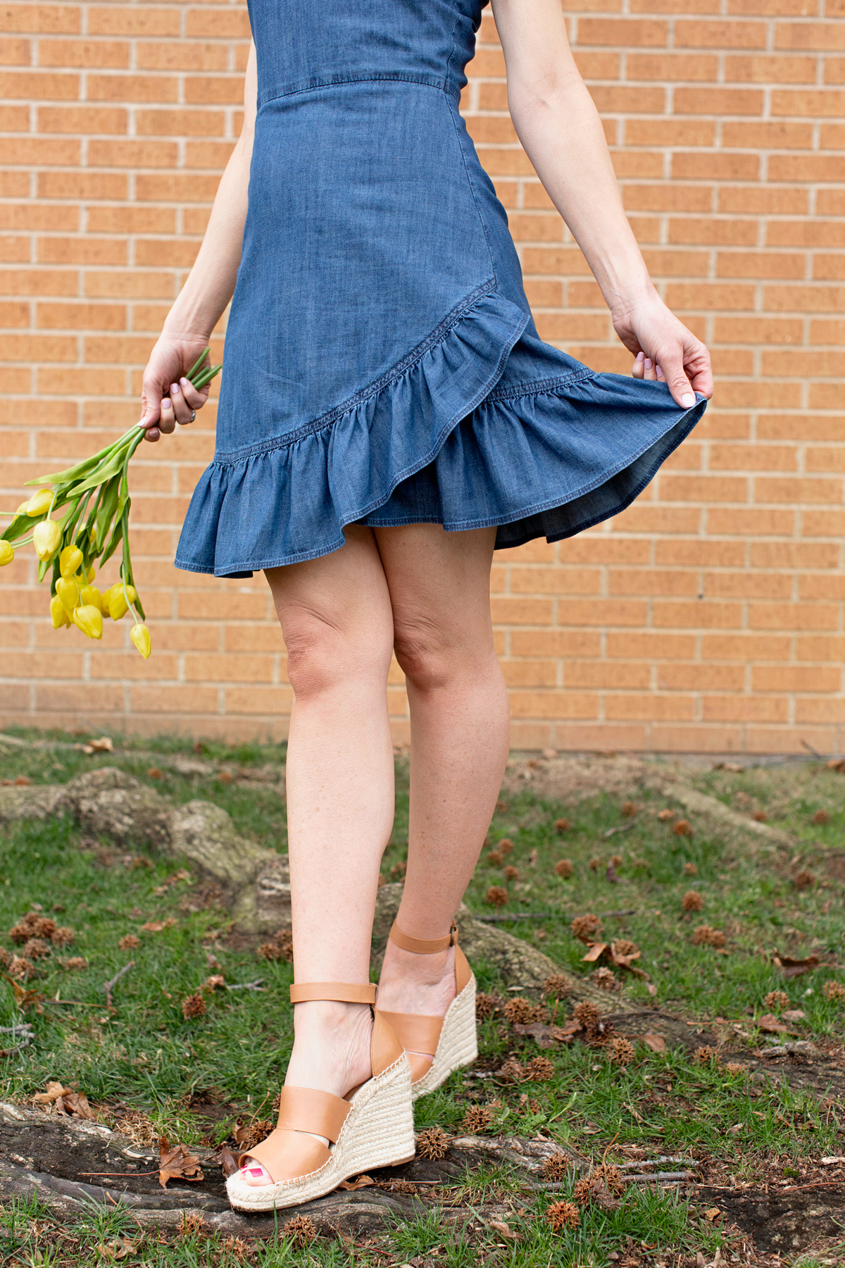 waist down of woman holding yellow flowers and skirt
