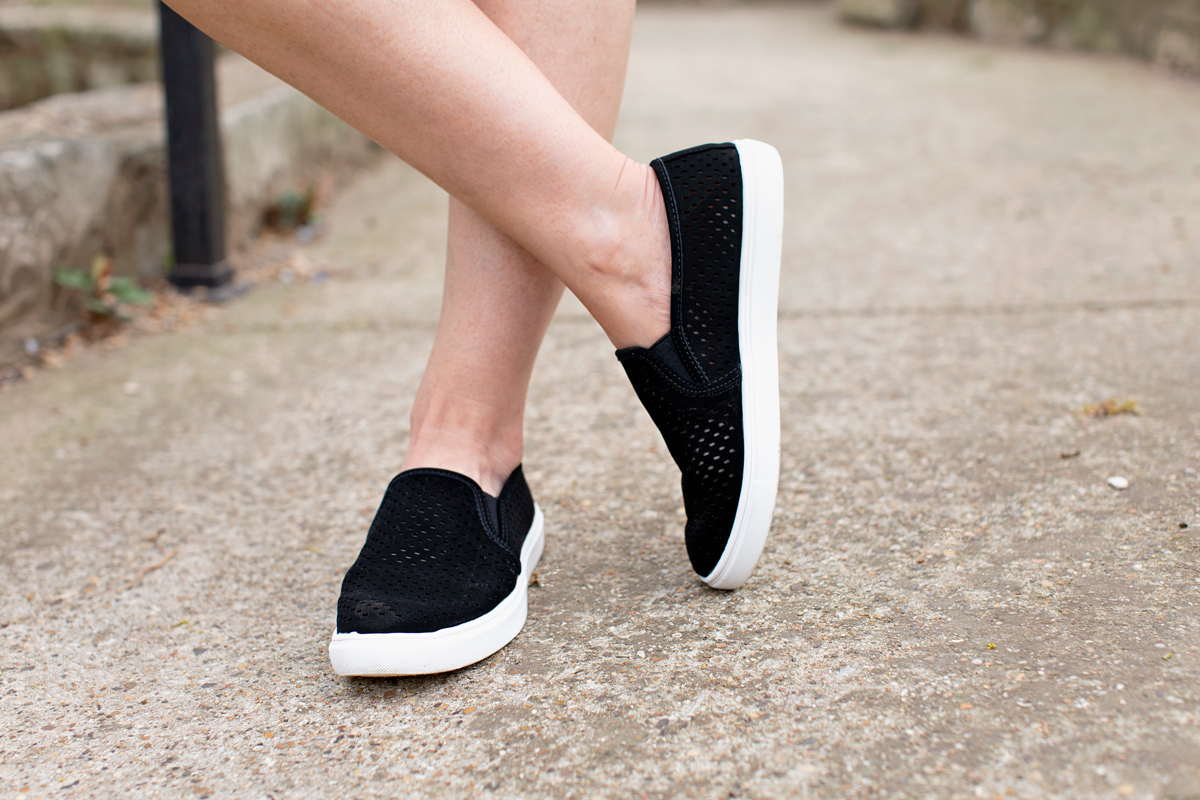 woman wearing black and white slip on tennies with one leg crossed over the other