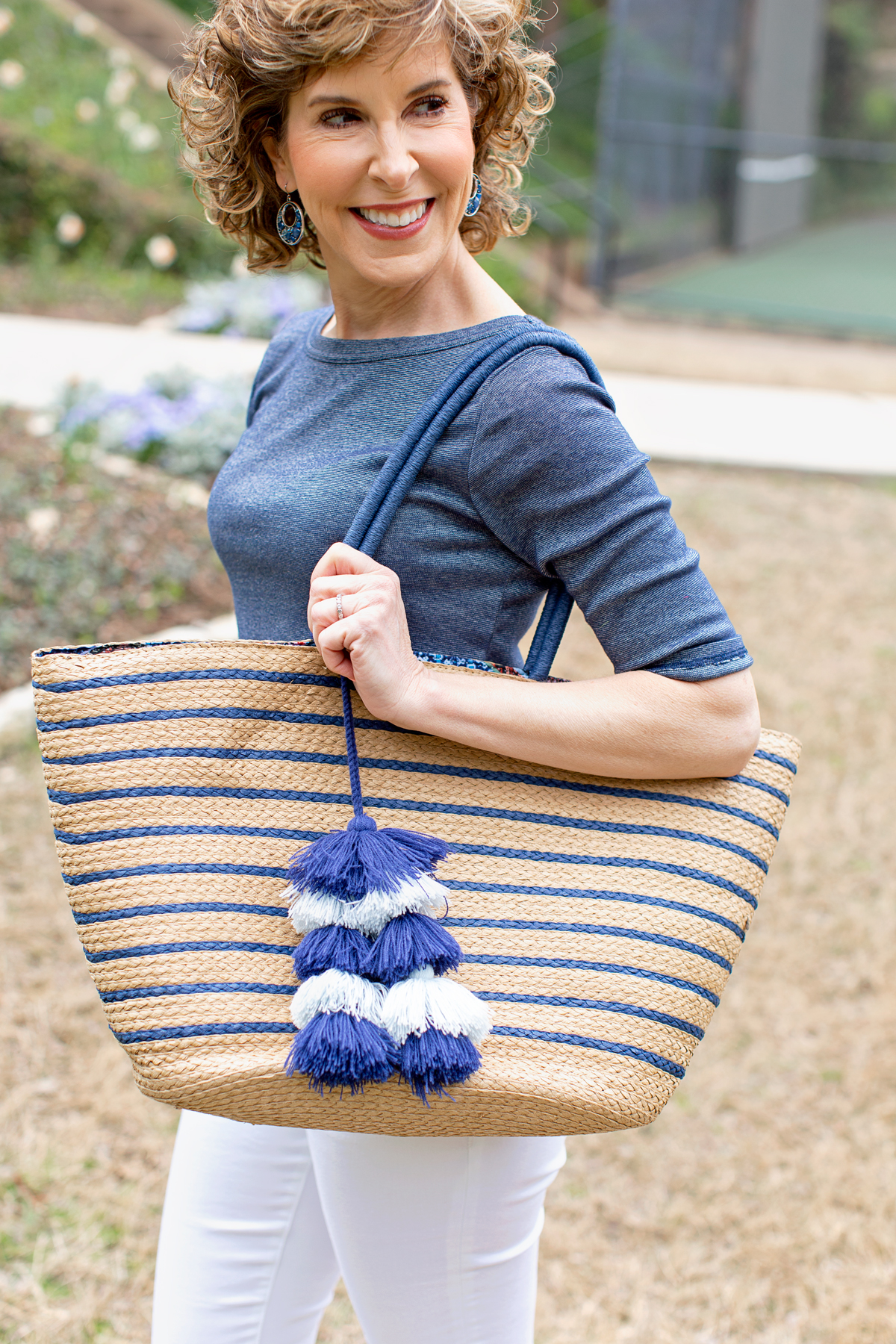 woman in blue tee carrying straw tote with tassels