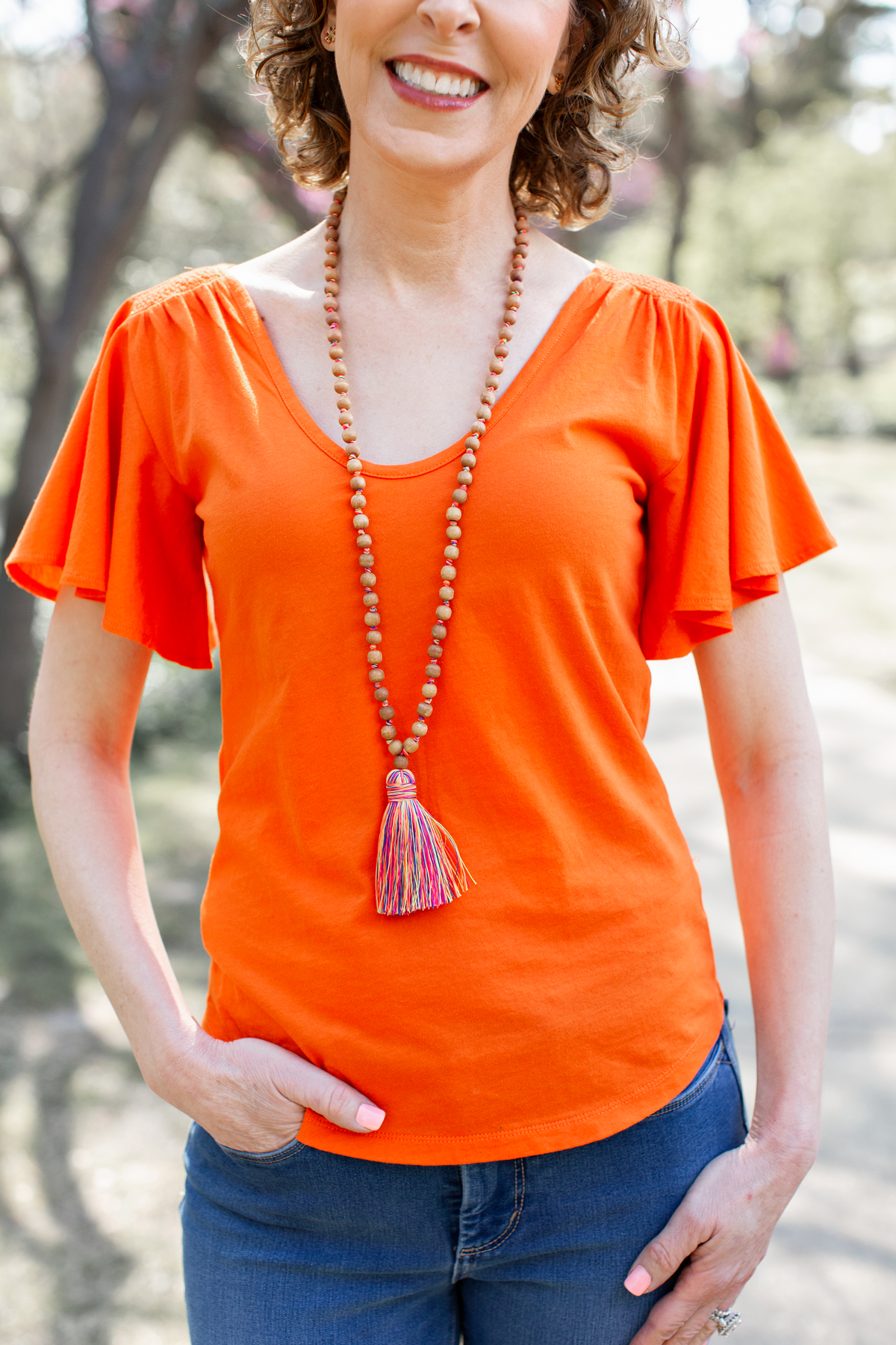 woman in orange shirt and tassel necklace in park