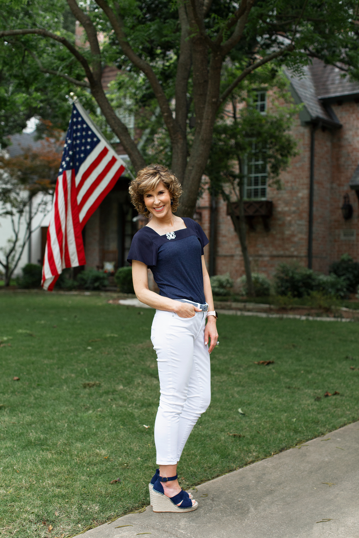 woman standing in front yard with flag