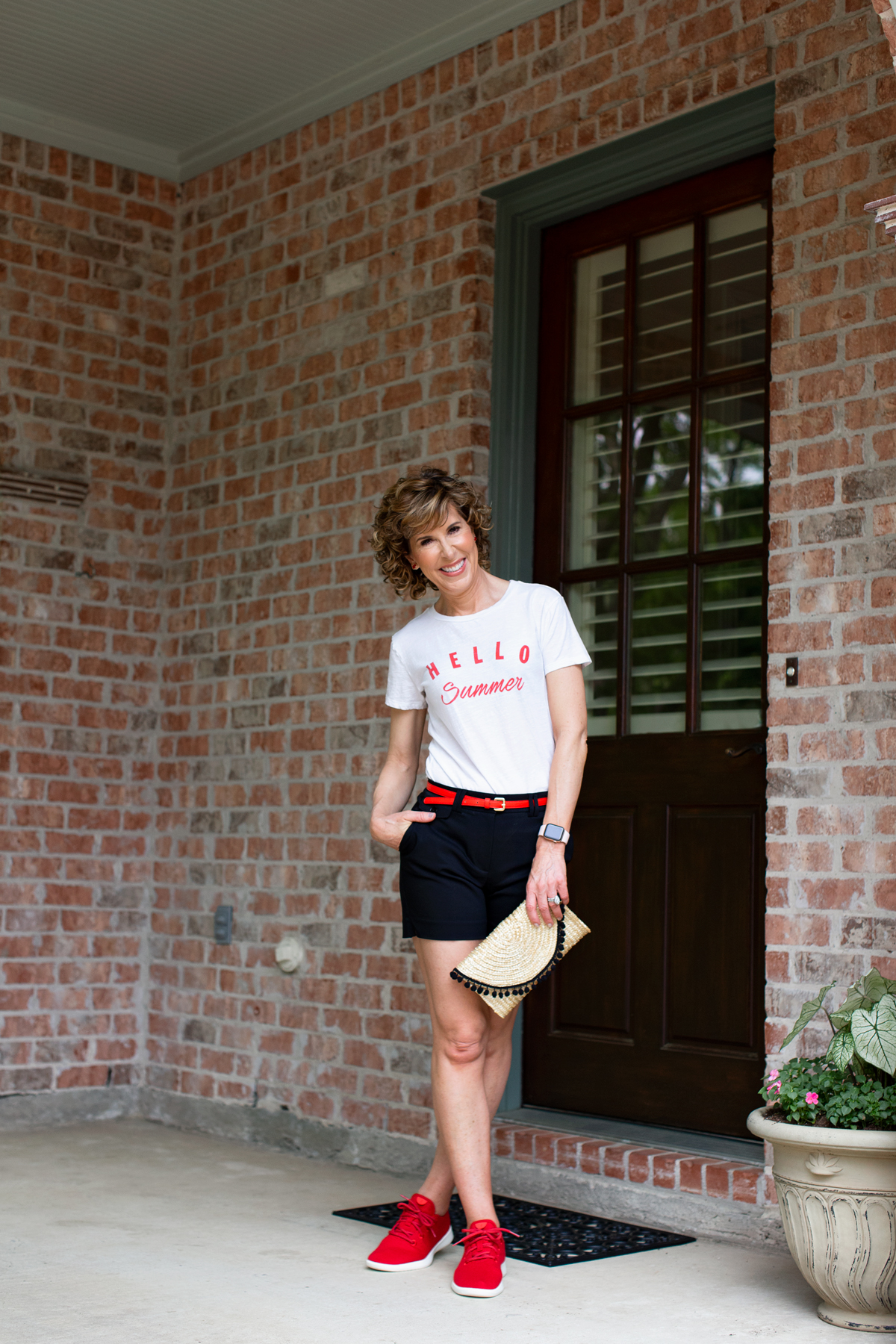 woman standing in front of a door wearing a hello summer tee from a brand with free shipping