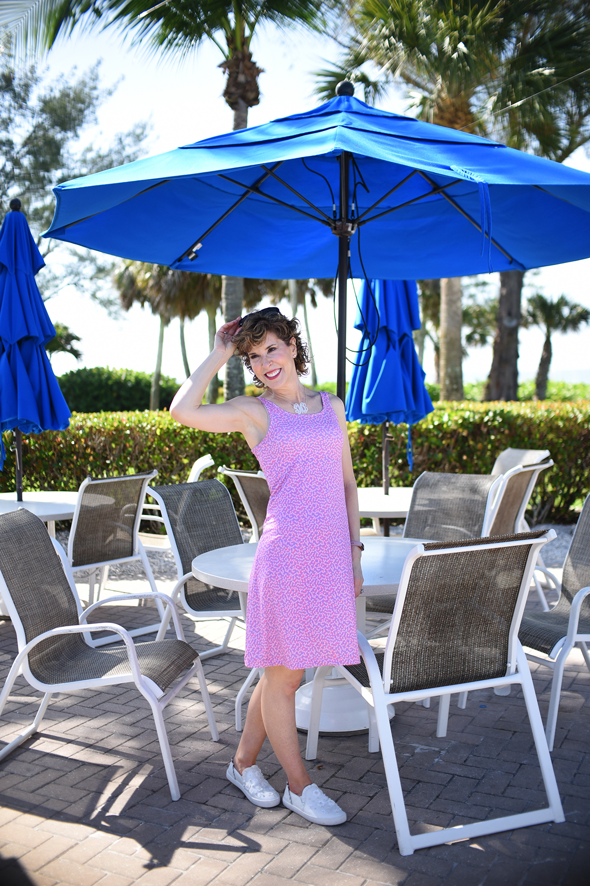 woman on beach vacation wearing pink dress standing under table with blue umbrella