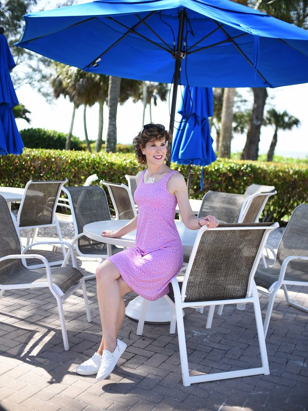 woman on beach vacation wearing pink dress sitting on arm of chair at table with blue umbrella