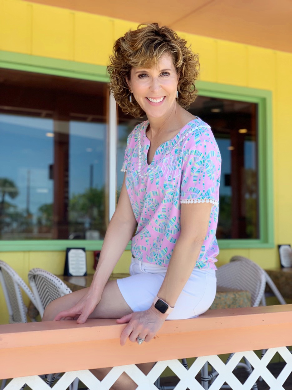 woman wearing tropical shirt sitting on railing of colorfully painted restaurant on sanibel island