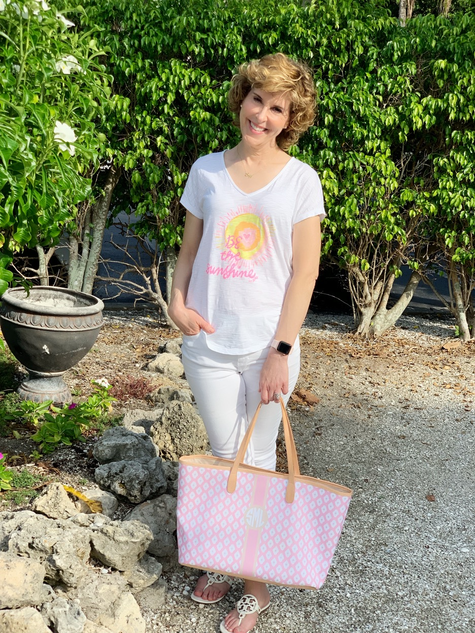 woman carrying pink bag in garden setting on sanibel beach trip travel outfit