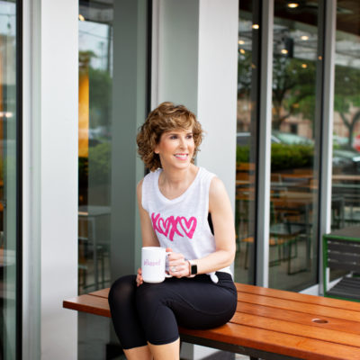 woman sitting on a table top drinking coffee and wearing xoxo tee