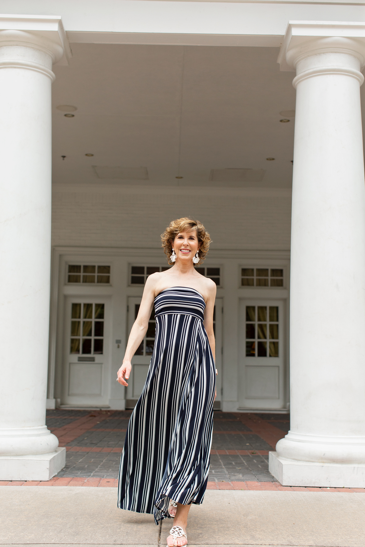 woman over fifty wearing summer statement earrings and blue and white maxi dress in front of a white building with columns