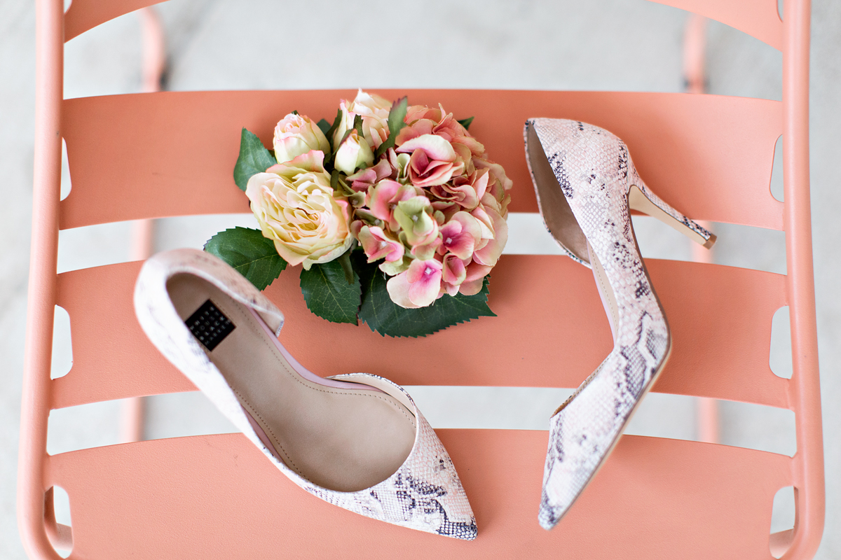 snake embossed pumps and a flower bouquet on a striped background