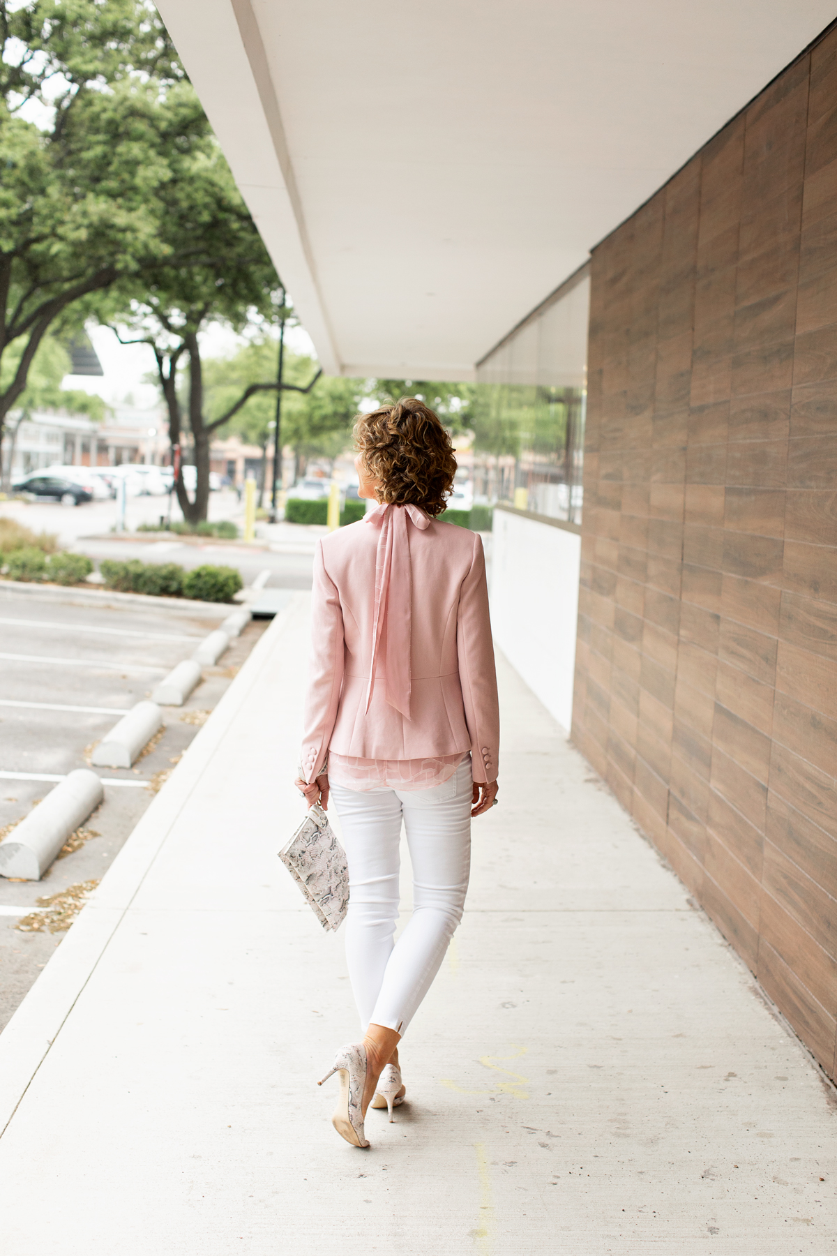 woman wearing pink blazer with a bow down the back