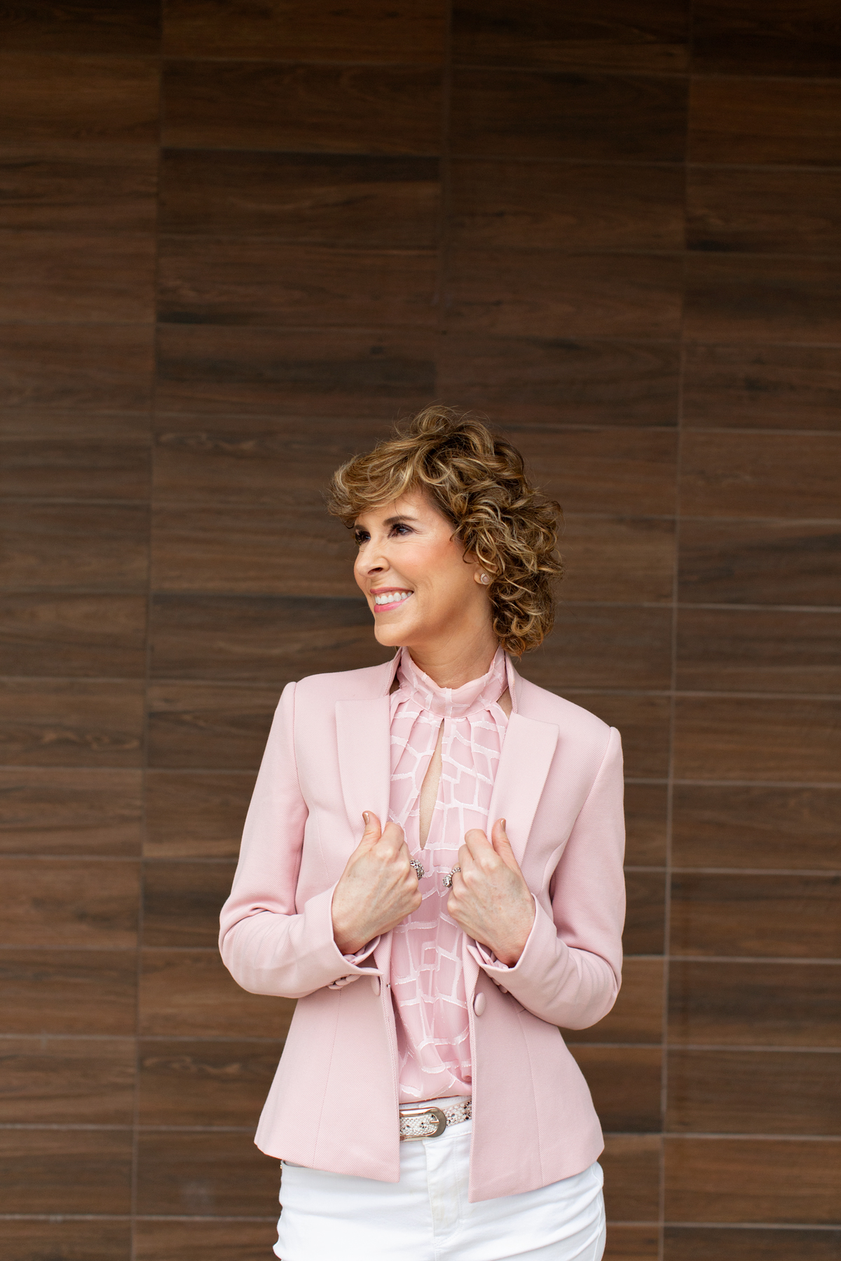 woman over fifty wearing pink top and blazer standing in front of a brown wall and looking to the side