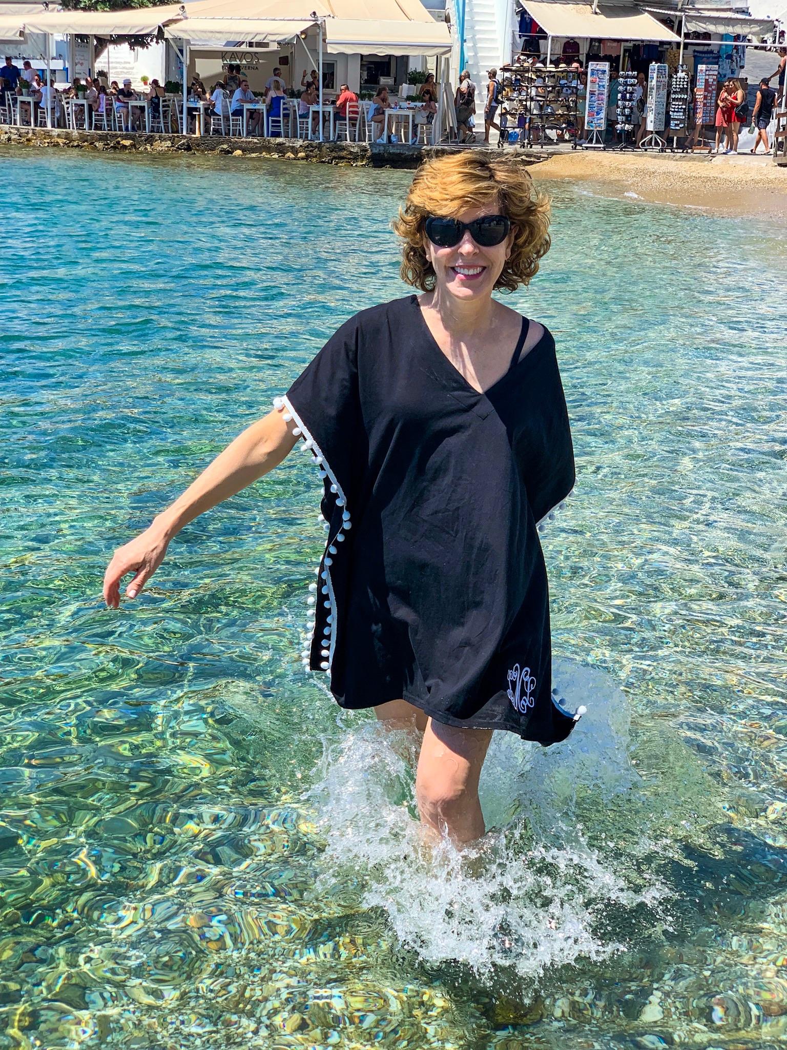 a woman wearing a black coverup in the water in mykonos greece