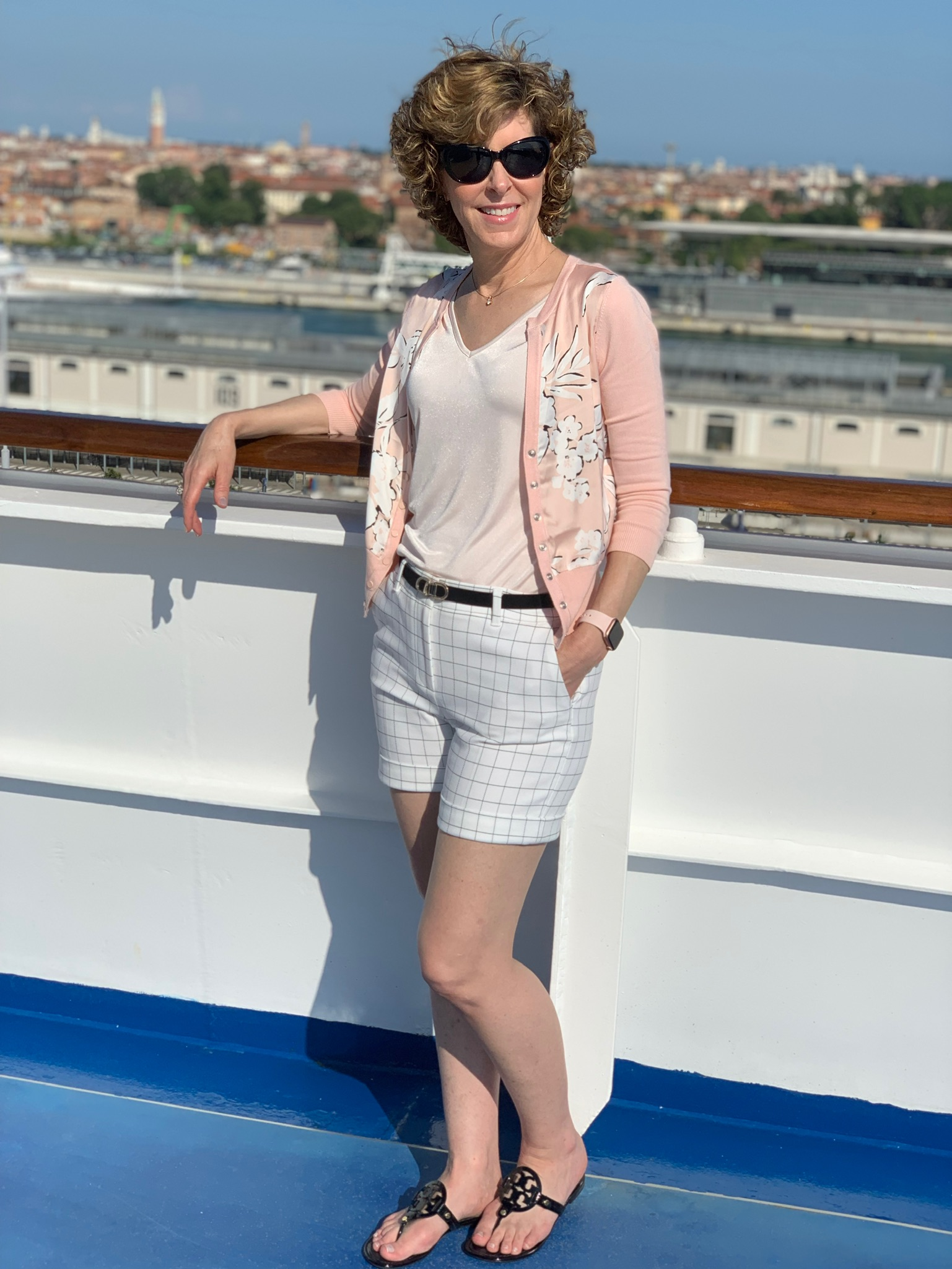 woman posing by rail of a cruise ship