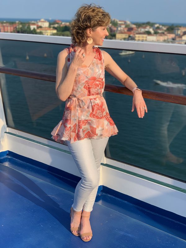 woman looking over the railing of a cruise ship