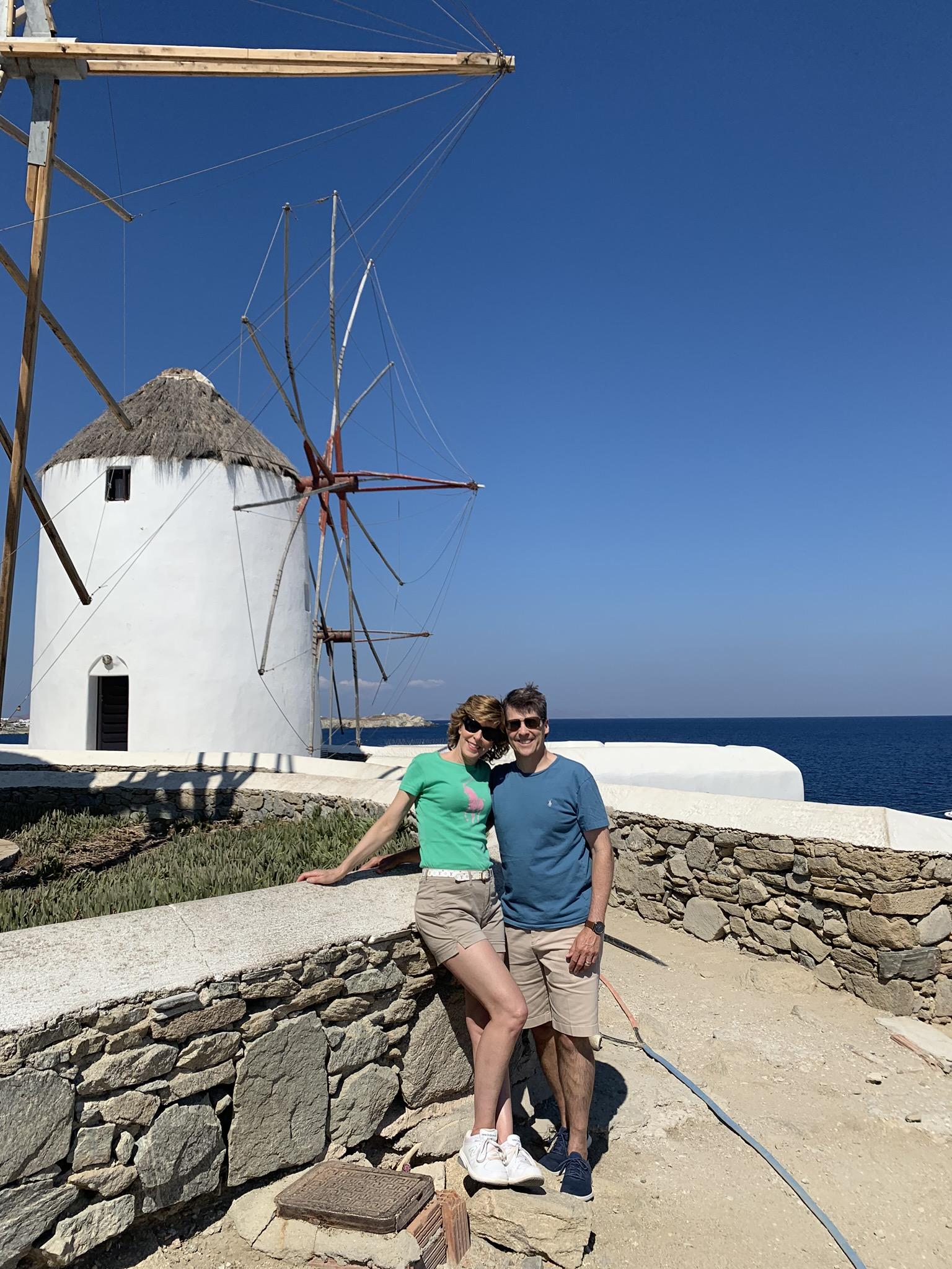 couple standing in front of windmills in mykonos greece