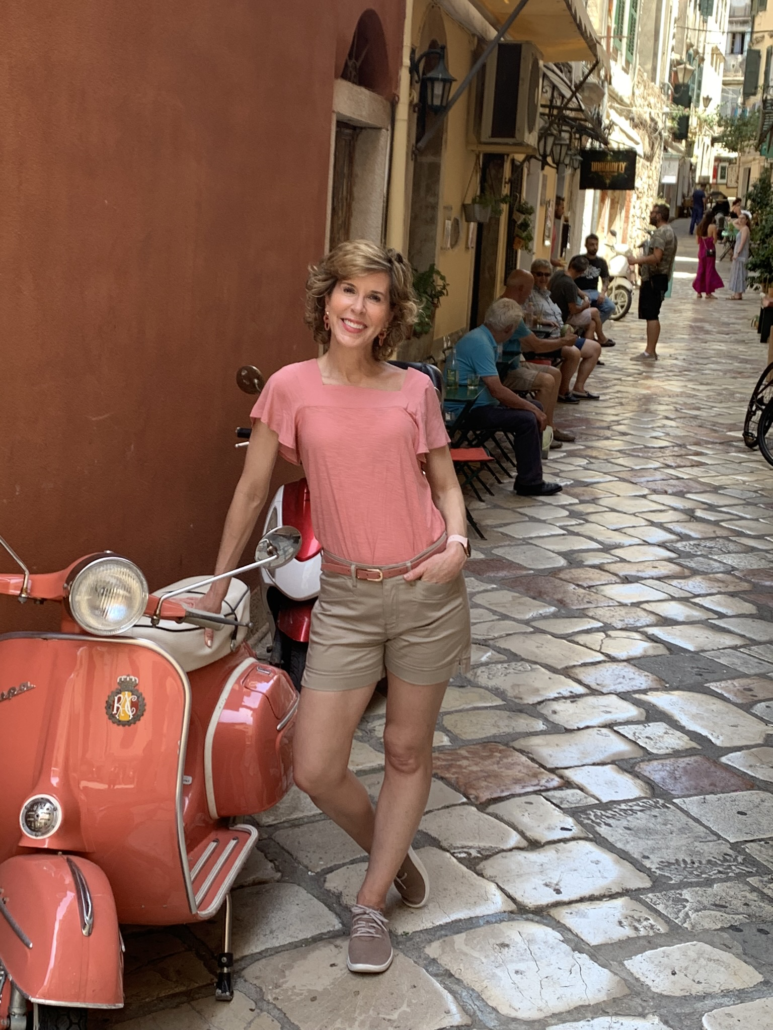 woman standing next to moped in the streets of dubrovnick