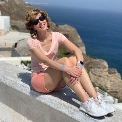 woman posing on a wall in santorini greece