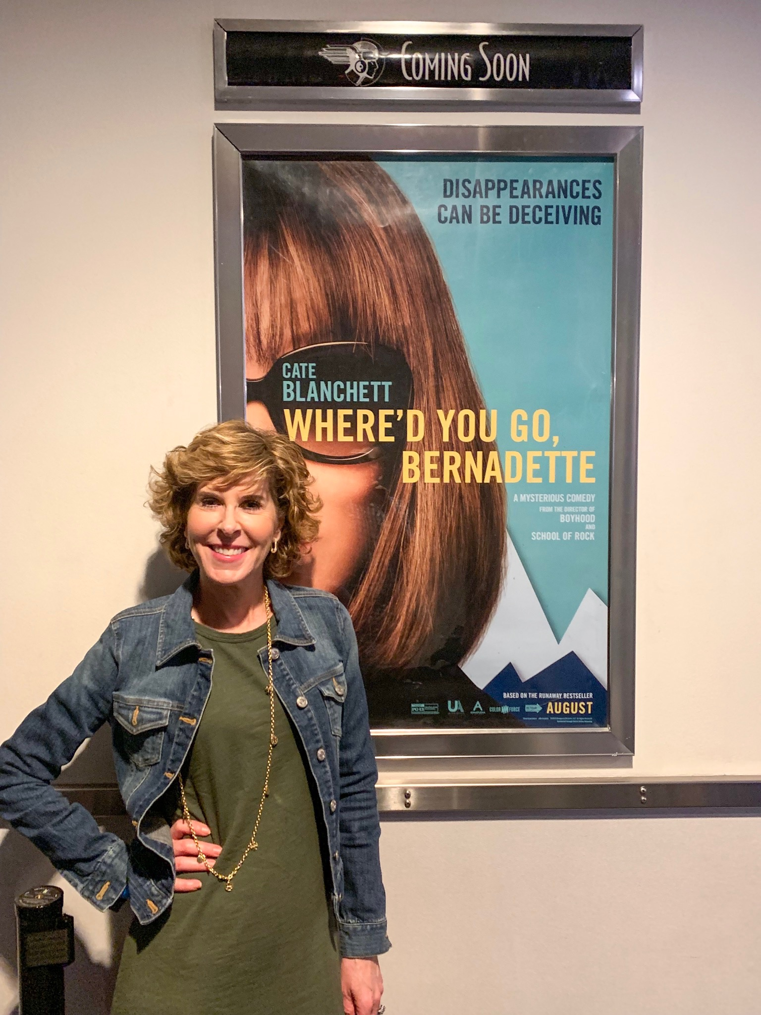 woman standing in front of movie poster