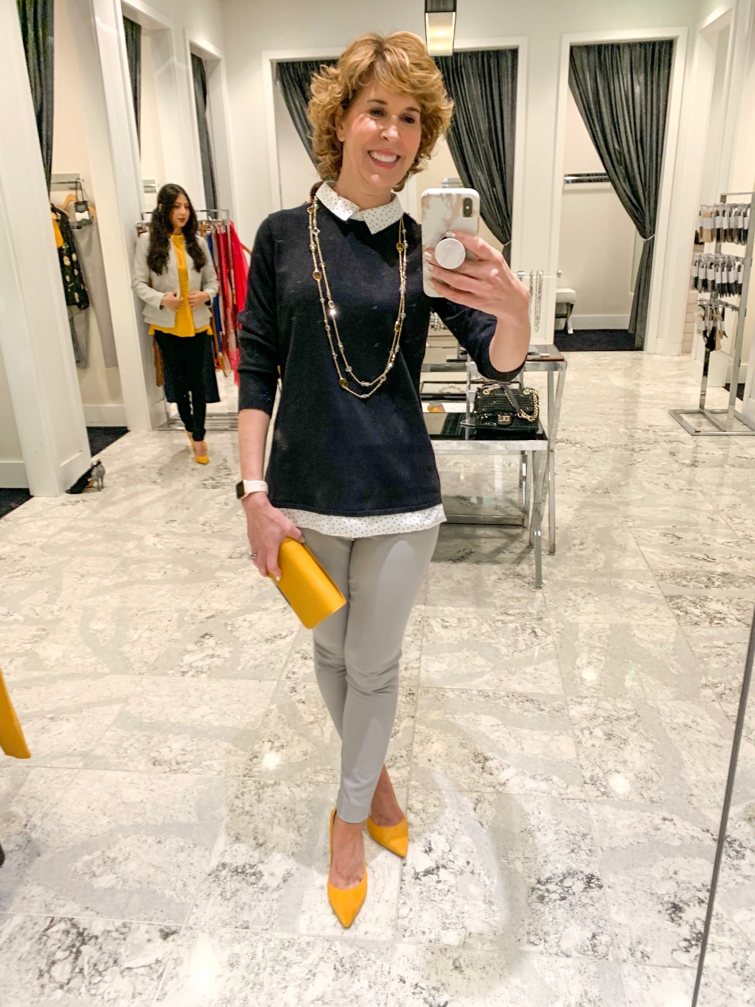 mirror selfie of woman carrying yellow clutch purse