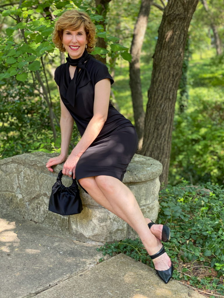empty nester woman wearing chico's black label cap sleeve dress sitting on a stone pedestal in the woods